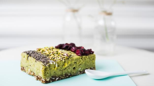 Diferentes tipos de fatia de bolo com chia; pistachios e coberturas de cranberries secas na tábua de cortar Foto gratuita