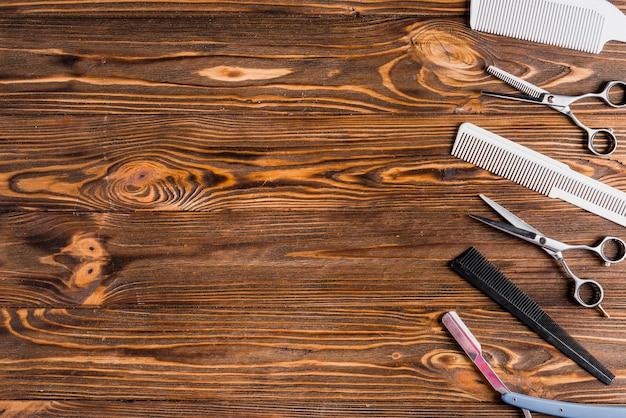 Diferentes tipos de ferramentas de barbeiro em uma linha na superfície de madeira Foto Premium