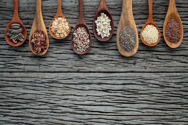 Diferentes tipos de grãos e cereais no fundo gasto de madeira Foto Premium