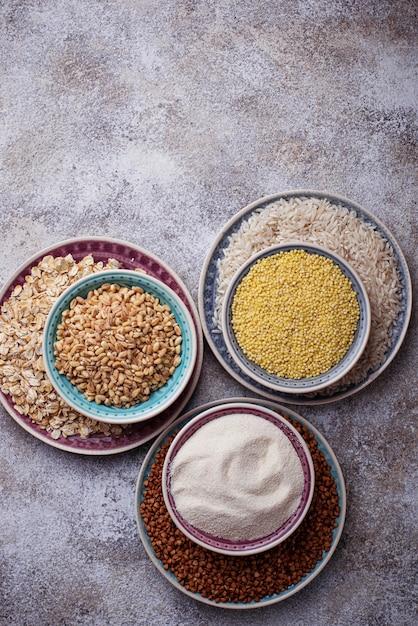 Diferentes tipos de grumos: arroz, sêmola, trigo, aveia, aveia, trigo mourisco. vista do topo Foto Premium