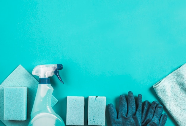 Diferentes tipos de itens de limpeza no fundo turquesa Foto gratuita