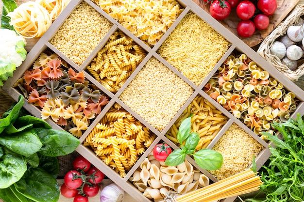 Diferentes tipos de macarrão cru italiano em caixa de madeira, macarrão de trigo integral, macarrão, espaguete, macarrão, tagliatelle. vista do topo. Foto Premium