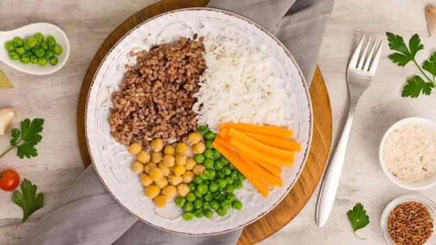 Diferentes tipos de mingau com legumes cozidos na placa de madeira Foto gratuita