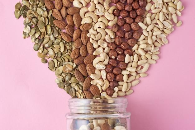 Diferentes tipos de nozes e sementes em uma jarra de vidro no fundo rosa Foto Premium