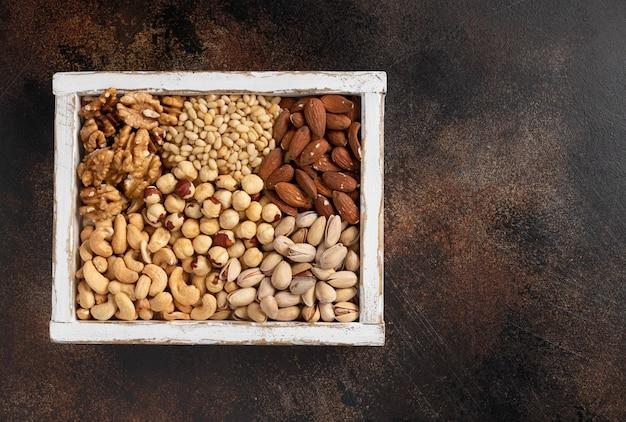 Diferentes tipos de nozes em uma caixa de madeira branca. alimentação saudável. Foto Premium