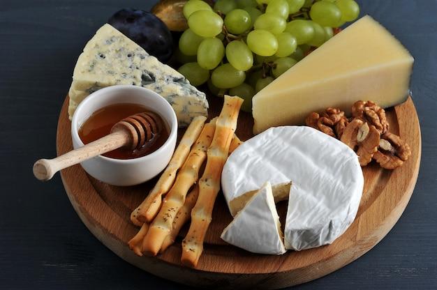 Diferentes tipos de queijo com mofo, uvas de mel e nozes Foto Premium