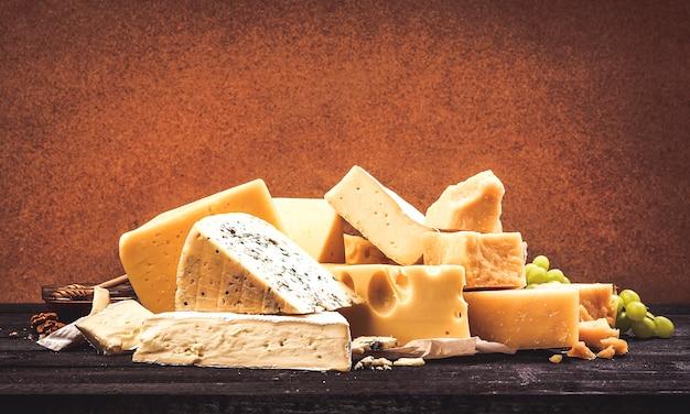 Diferentes tipos de queijo na mesa de madeira preta Foto Premium