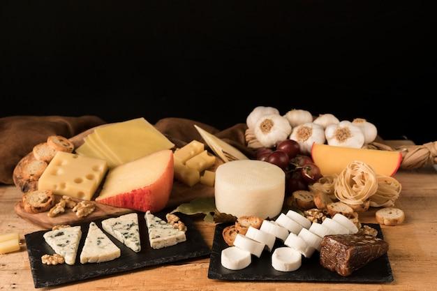 Diferentes tipos de queijos organizar em pedra ardósia na mesa de madeira Foto Premium