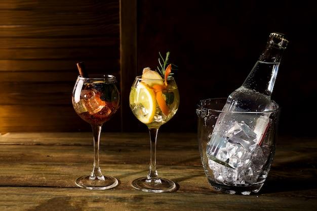 Diferentes tipos de whisky com base em cocktails com balde de gelo de vidro no backgorund de madeira escura Foto Premium