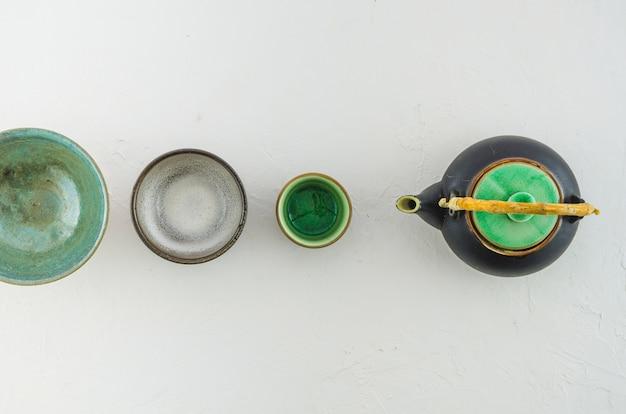 Diferentes tipos de xícaras de chá e bule em fundo branco Foto gratuita