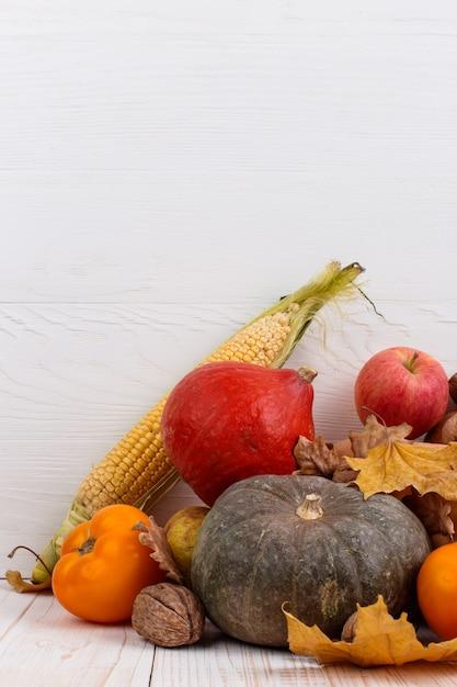 Diferentes vegetais, abóboras, maçãs, peras, nozes, milho, tomate e folhas secas em fundo branco de madeira. colheita de outono, copyspace. Foto Premium