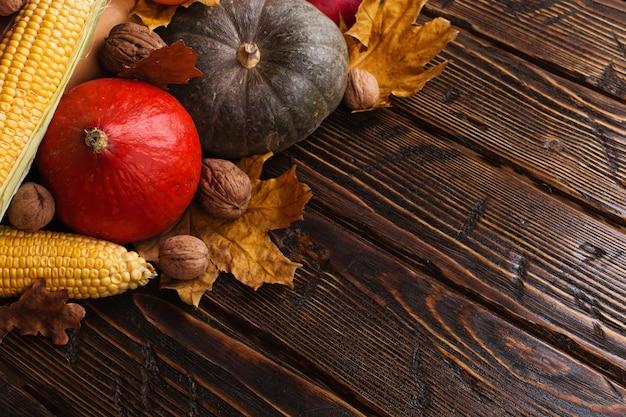 Diferentes vegetais, abóboras, maçãs, peras, nozes, tomate, milho, folhas secas de amarelas sobre fundo de madeira. humor de outono, copyspace. colheita. Foto Premium