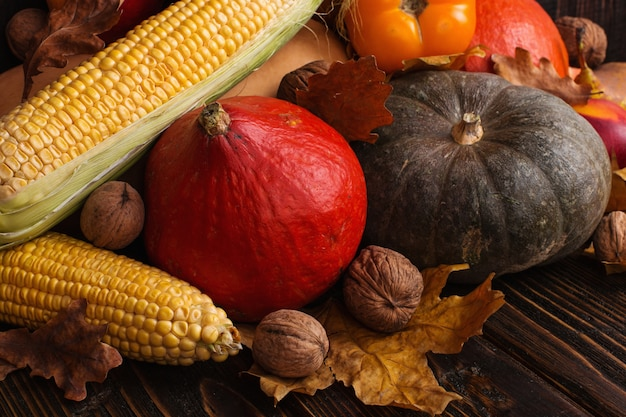 Diferentes vegetais, abóboras, maçãs, peras, nozes, tomate, milho, folhas secas de amarelas sobre fundo de madeira. humor de outono, plana leigos. colheita. Foto Premium