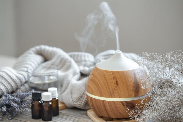 Difusor de óleo de aroma moderno em superfície de madeira com elemento de malha, água e óleos em potes. Foto gratuita