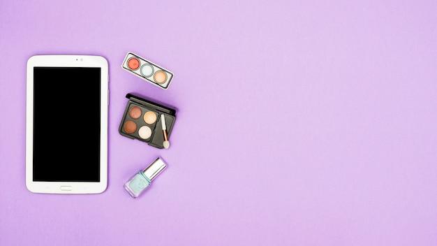 Digital tablet com paleta de sombra e unha polonês garrafa no fundo roxo Foto gratuita