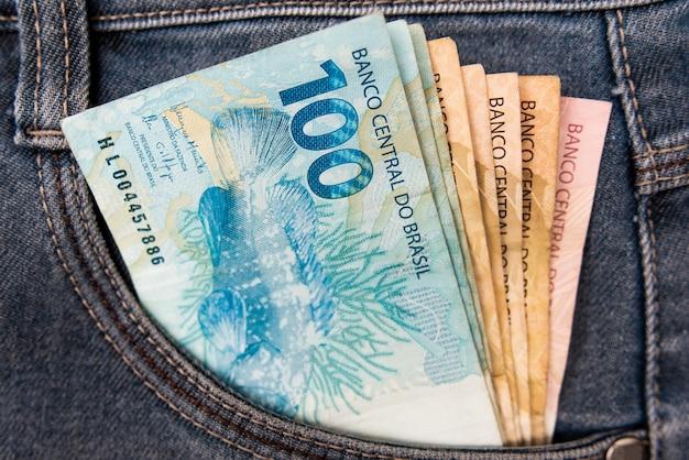 Dinheiro brasileiro no bolso da calça jeans, conceito de finanças. moeda brasil Foto Premium