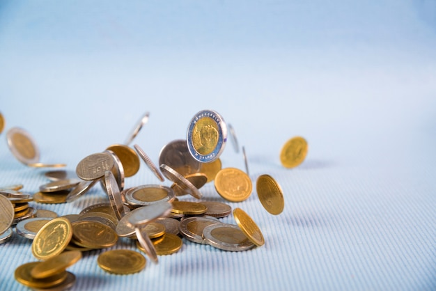Dinheiro caindo moedas em fundo azul Foto Premium
