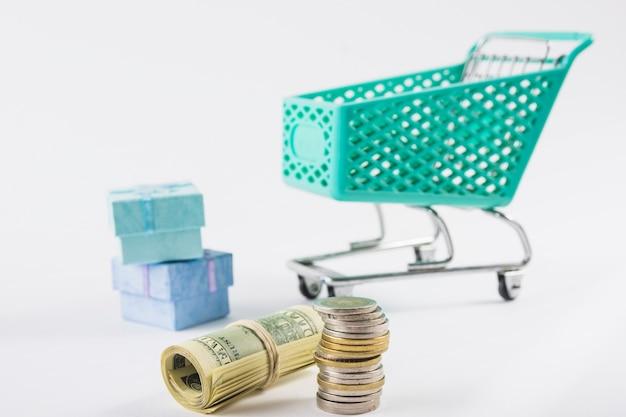Dinheiro com carrinho de supermercado pequeno na mesa Foto gratuita