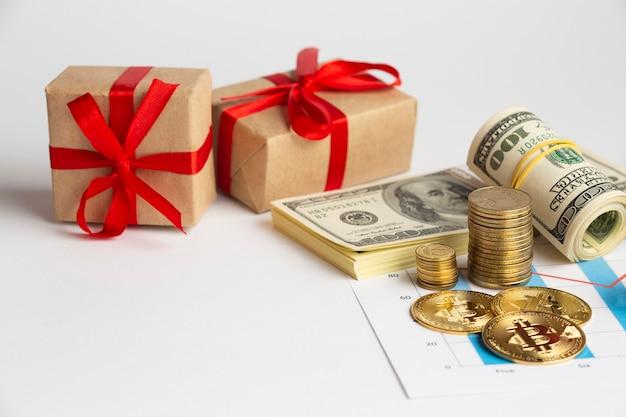 Dinheiro de alto ângulo empilha perto de presentes Foto gratuita
