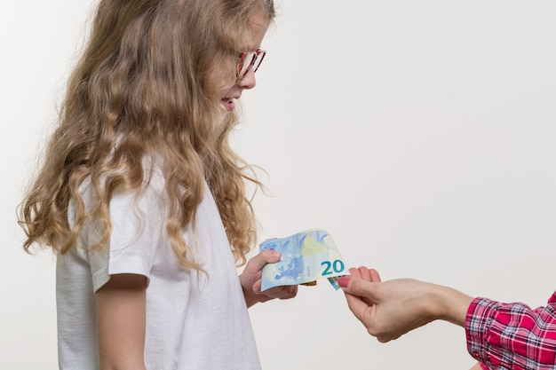 Dinheiro de bolso. mãe dá dinheiro à criança. Foto Premium