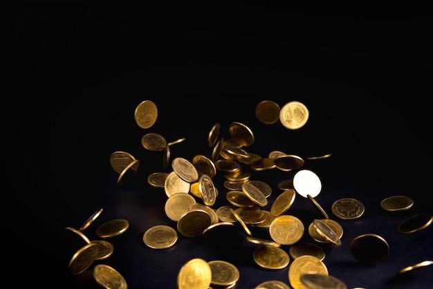 Dinheiro de moedas de ouro caindo no fundo escuro Foto Premium