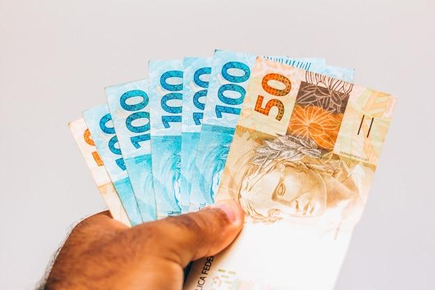 Dinheiro do brasil. notas reais, dinheiro brasileiro na mão de um homem negro. notas de 100 e 50 reais. conceito de inflação, economia e negócios. luz de fundo Foto Premium