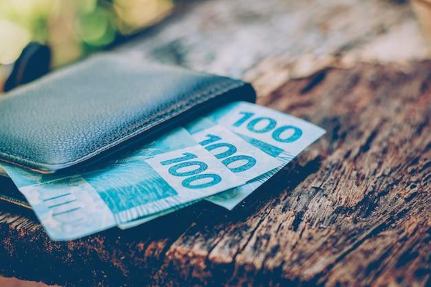 Dinheiro do brasil. notas reais, moeda brasileira dentro de uma carteira preta. conceito de finanças, economia e riqueza. Foto Premium