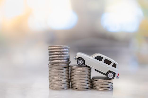 Dinheiro, empréstimo e poupança. feche acima do brinquedo mini carro branco em miniatura em cima da linha da pilha de moedas de prata. Foto Premium