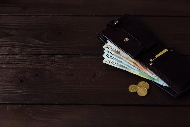 Dinheiro na carteira. euro dinheiro na carteira marrom no fundo de madeira Foto gratuita