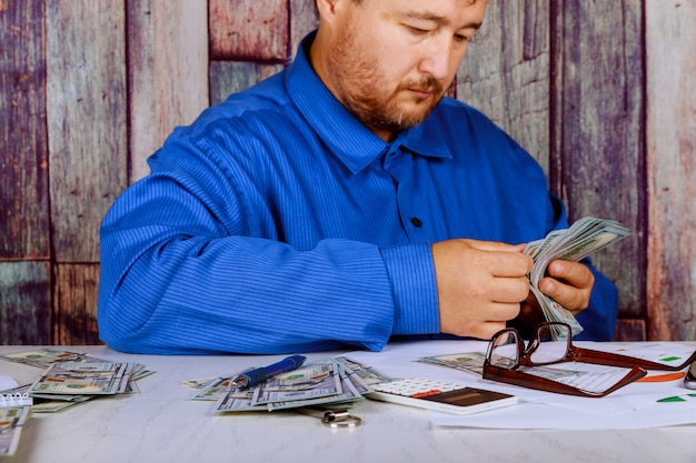 Dinheiro no homem de mãos contando dinheiro dólares nas mãos do homem um homem em roupas de negócios com dólares. Foto Premium