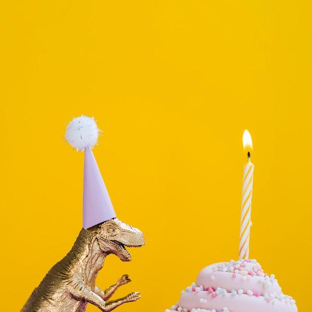 Dinossauro com chapéu de aniversário e delicioso bolinho Foto gratuita
