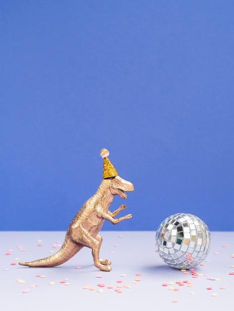 Dinossauro engraçado com chapéu de aniversário e globo de discoteca Foto gratuita