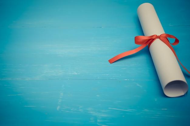 Diploma com fita vermelha na madeira Foto Premium