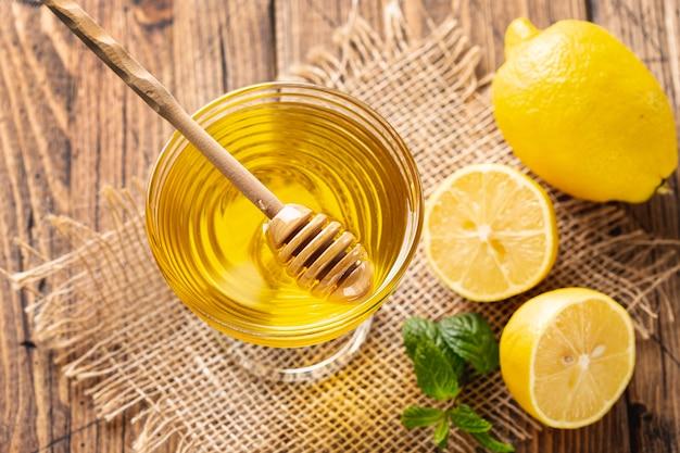 Dipper em uma tigela de mel com limões Foto gratuita