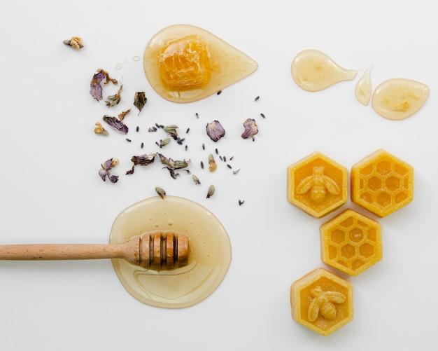 Dipper mel com cera de abelha e flores secas Foto gratuita