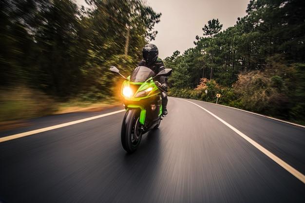 Dirigindo a motocicleta de cor verde neon na estrada na hora do crepúsculo. Foto gratuita