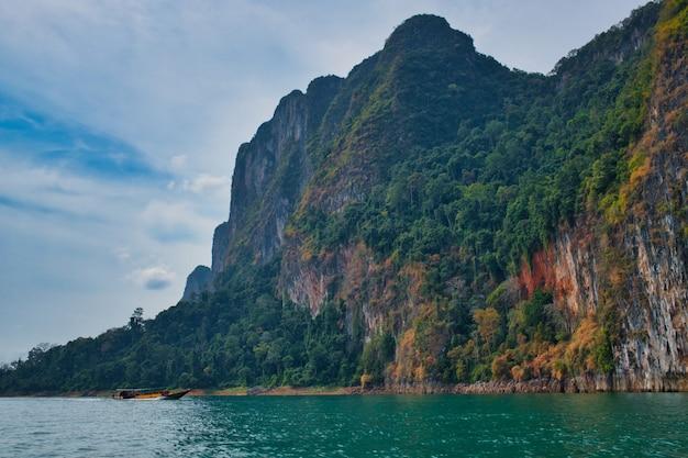 Dirigindo longtailboat no lago khao sok, na tailândia, em uma bela paisagem rochosa Foto gratuita