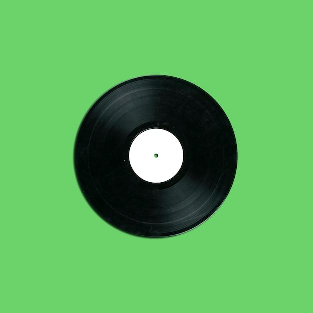 Disco de vinil retrô com etiqueta branca em branco sobre fundo verde Foto Premium