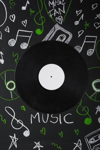 Disco de vinil sobre o quadro-negro com notas musicais desenhadas Foto gratuita