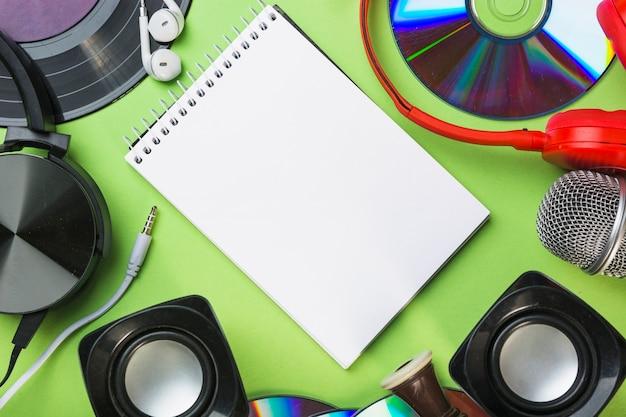 Discos compactos; alto falante; fone de ouvido; fone de ouvido ao redor do bloco de notas em espiral sobre fundo verde Foto gratuita