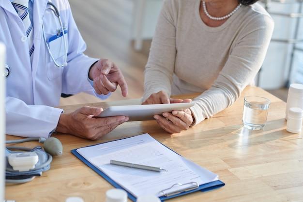 Discutindo registros com paciente sênior Foto gratuita