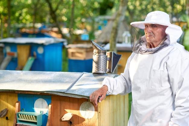 Disparado de um apicultor no terno de apicultura em pé perto da linha de colméias em seu copyspace apiário. Foto gratuita