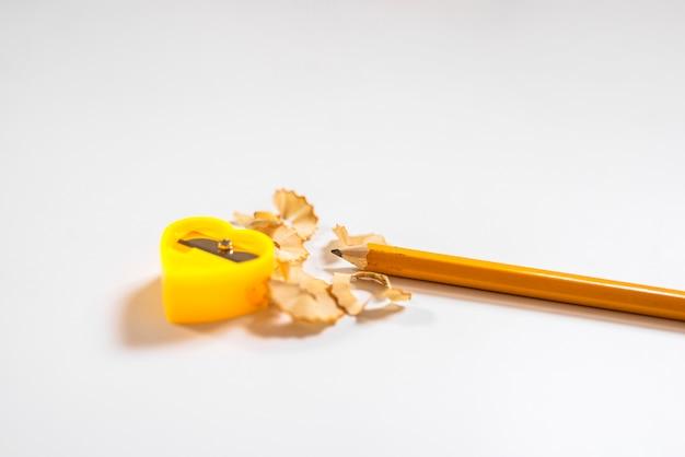 Disparo de afiadores de lápis amarelos. lápis de afiação com lápis colorido. aparas isoladas no fundo branco Foto Premium