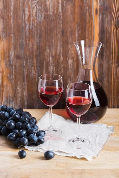 Disposição de copos e jarra de vinho Foto gratuita