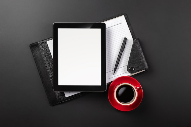 Dispositivo do tablet pc na mesa do homem de negócios e no copo de café. vista superior com espaço para texto Foto Premium