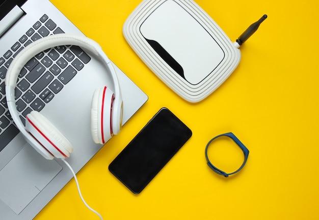 Dispositivos e acessórios digitais modernos. laptop, smartphone, pulseira inteligente, fones de ouvido, roteador wi-fi em um fundo amarelo. Foto Premium