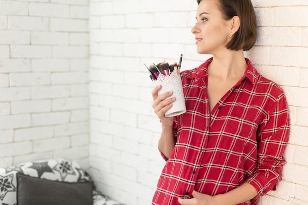 Distraído, mulher, segurando pincéis de maquiagem Foto gratuita