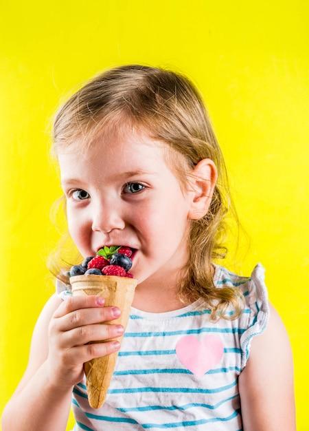 Diversão de verão férias conceito, menina criança loira bonita comer bagas de casquinha de sorvete waffle, fundo amarelo brilhante Foto Premium