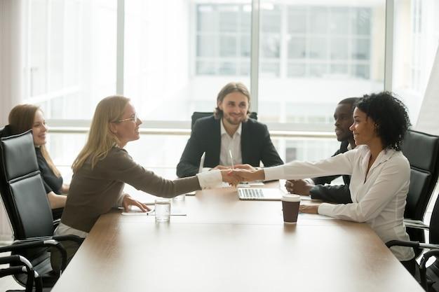 Diversas empresárias sorridentes cumprimentando na reunião do grupo multirracial de mãos Foto gratuita