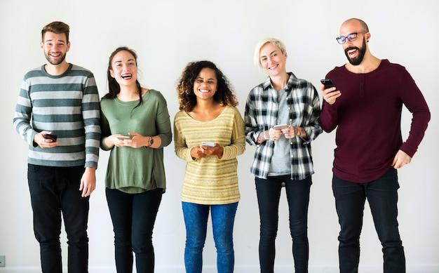 Diversas pessoas em pé com seus celulares na mão Foto Premium